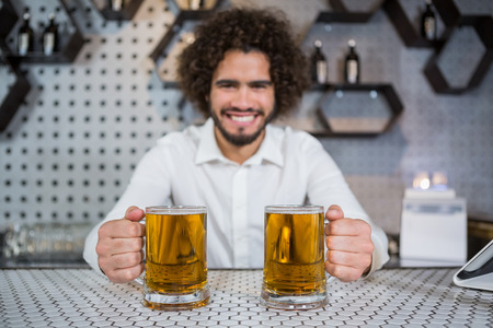Portrait of smiling bartender holding two glass of beer in bar counter at bar Stock Photo