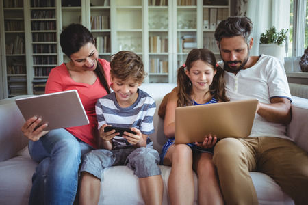Happy family sitting on sofa and using laptop, mobile phone and digital tablet at home Фото со стока - 64373221