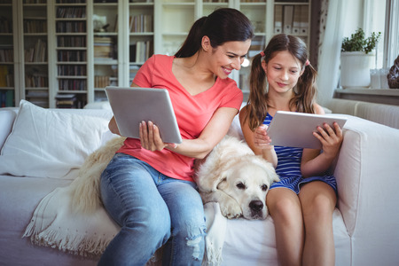 classy house: Mother and daughter sitting with pet dog and using digital tablet at home Stock Photo