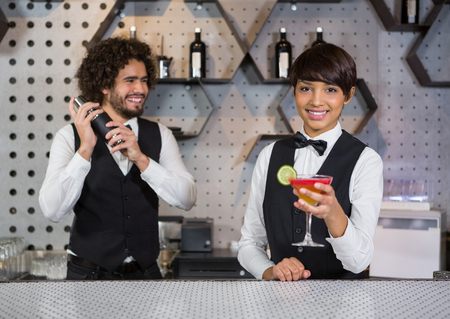 bartenders: Two bartenders preparing cocktail and serving in bar counter at bar Stock Photo