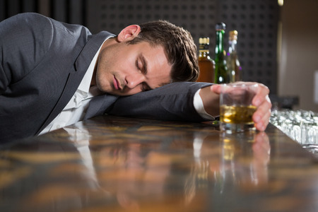 inebriated: Drunk man lying on a counter with glass of whisky at bar Stock Photo