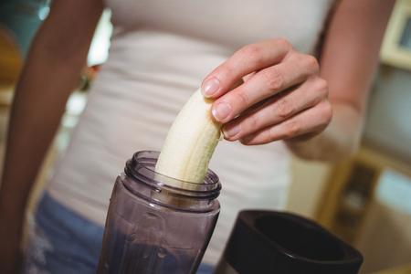 licuado de platano: Mid section of woman preparing banana smoothie