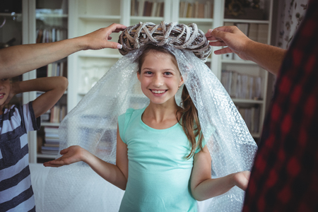 classy house: Girl imitating to be an angel by wearing a bubble wrap and an unpacked ring in the new house Stock Photo