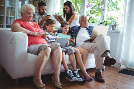Multi-generation family sitting on sofa and using laptop, mobile phone and digital tablet Stock Photo - 64381873