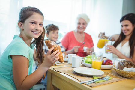 Smiling girl eating a croissant while having breakfast with family