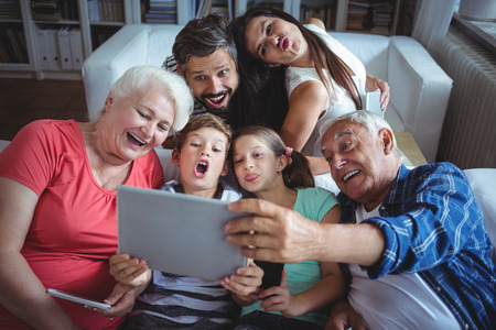multigeneration: Multi-generation family taking a selfie on digital tablet in living room at home