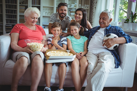 multigeneration: Multi-generation family sitting on sofa with popcorn and pizza while watching soccer match Stock Photo