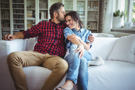 Man kissing woman while sitting on sofa in living room at home Stock Photo