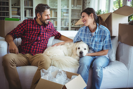 Couple sitting on sofa with their pet dog in their new house Stock Photo