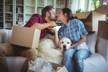 each other: Young couple kissing each other while unpacking carton boxes in new house