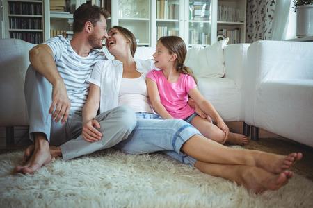 Glückliche Familie auf dem Teppich im Wohnzimmer zu Hause sitzen