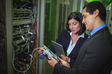 analyzer: Technicians using digital cable analyzer while analyzing server in server room Stock Photo