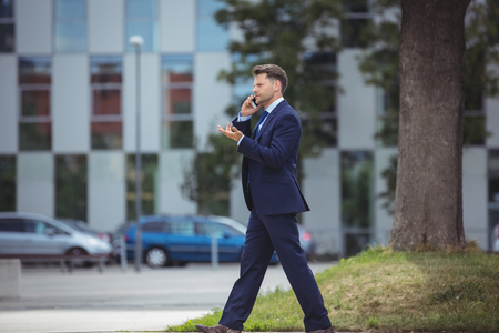 Businessman talking on mobile phone while walking on road