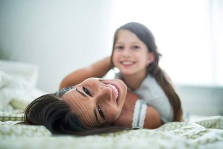nightwear: Portrait of mother and daughter lying in bedroom at home