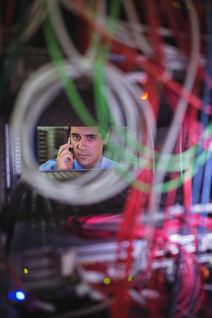 mounted: Technician talking on mobile phone while checking cables in a rack mounted server Stock Photo