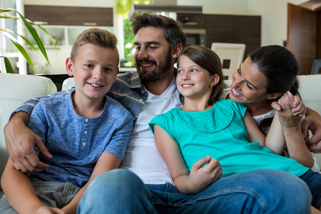 family sofa: Happy family sitting with arm around on sofa at home Stock Photo
