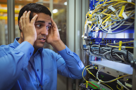 Technician getting stressed over server maintenance in server room Stock Photo