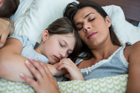 Mother and daughter sleeping together in bedroom at home