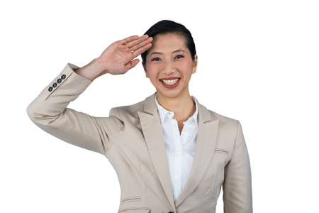 saluting: Portrait of businesswoman saluting against white background