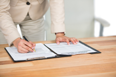 midsection: Mid-section of businesswoman filling insurance contract form in office