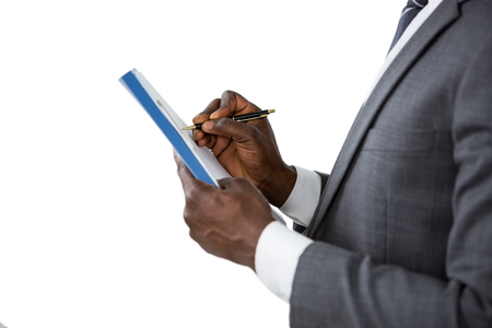 domestic policy: Close-up of mans hands signing insurance document at desk Stock Photo