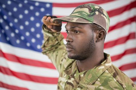 saluting: Close- up of soldier saluting against american flag Stock Photo
