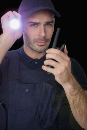 walkie talkie: Security officer holding a torch and talking on walkie talkie against black background Stock Photo