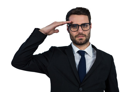 saluting: Portrait of businessman saluting against white background Stock Photo