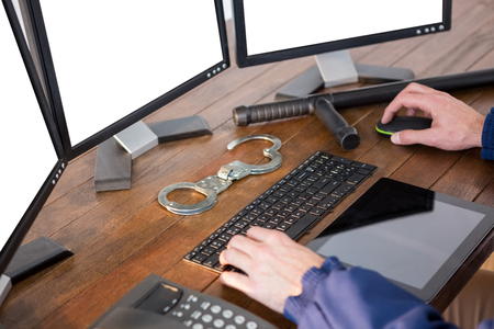 hand cuff: Hands of security officer using computer at desk Stock Photo