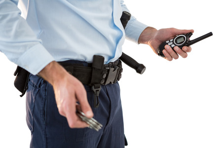 hand cuff: Mid section of security officer holding a walkie-talkie against white background