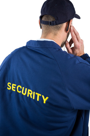 earpiece: Rear view of security officer listening to earpiece against white background