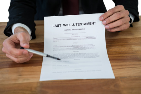 domestic policy: Mid section of businessman showing last will and testament form against white background Stock Photo