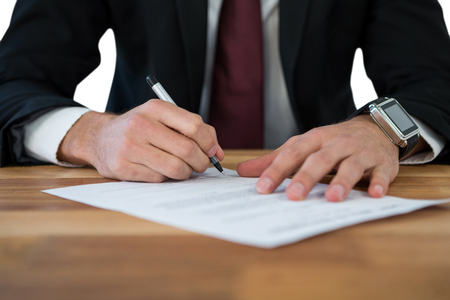 domestic policy: Mid-section of businessman filling last will and testament form against white background Stock Photo