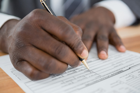 Close-up of mans hand signing a document at desk