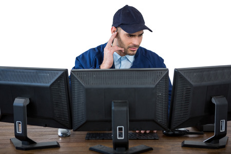 earpiece: Security officer listening to earpiece while using computer against white background