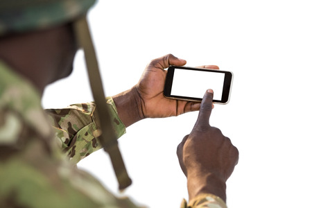 Soldier using a mobile phone against white background