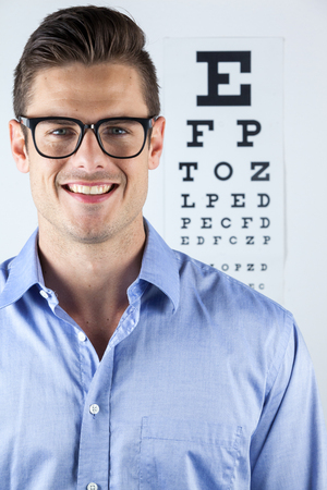 eye chart: Portrait of man wearing spectacles with eye chart in background