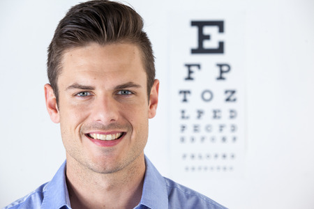 eye chart: Portrait of man wearing contact lens with eye chart in background