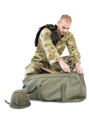 solider: Solider packing his bag against white background