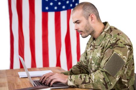 solider: Solider using a laptop at desk against white background Stock Photo
