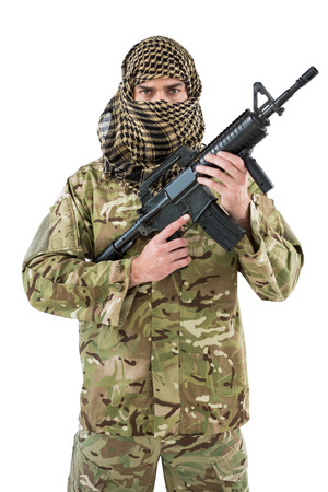 militant: Portrait of soldier holding a rifle against white background