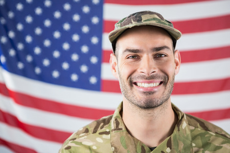 militant: Close-up of smiling soldier against american flag Stock Photo