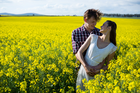 Romantic couple standing in mustard field on a sunny day