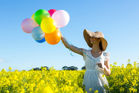 mustard field: Woman holding colorful balloons in mustard field on a sunny day