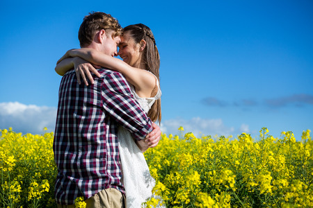 Romantic couple embracing each other in mustard field on a sunny day Stock Photo