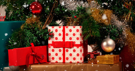 christmas tree presents: Snow falling against close-up of various presents and christmas tree Stock Photo
