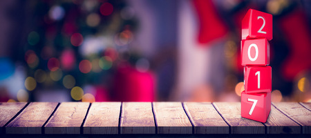domicile: Composite image of numbers stack of cubes against defocused of christmas tree lights and fireplace