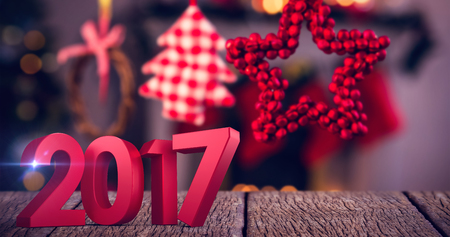 Composite image of number in red against christmas ornaments hanging on ribbon Stock Photo
