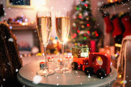 room decoration: Snow falling against champagne flutes with christmas decorations on table Stock Photo