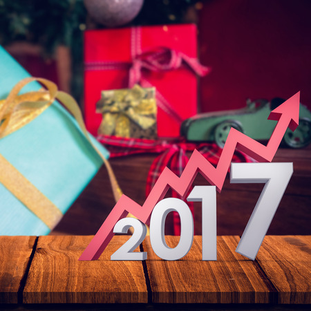 digitally generated image: Digitally generated image of number with arrow against wrapped gifts on wooden trolley Stock Photo